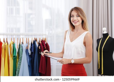 Beautiful young stylist holding clipboard near rack with designer clothes in studio