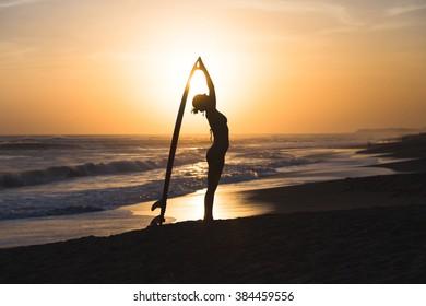 Beautiful young surfer girl in bikini with surfboard on a beach