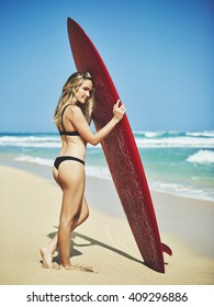 Beautiful young surfer girl on the beach with classic vintage surfboard