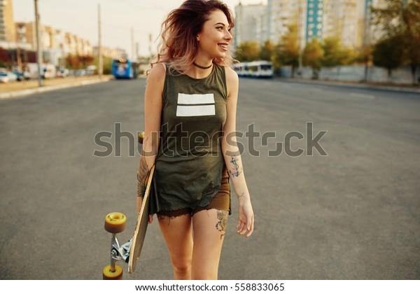 Schöne junge tätowierte Frau mit seinem Langboard auf der Straße in der Stadt bei sonnigem Wetter