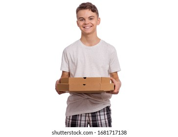 Beautiful young teen boy holds cardboard box with pizza in his hands, isolated on white background. Male student makes pizza delivery. Happy child.
