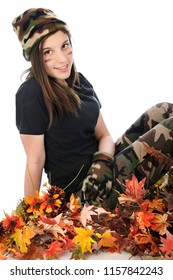 A beautiful young teen in camouflage happily sitting among colorful fall foliage.  On a white background.