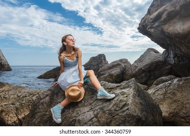 Beautiful young teen girl in dress and hat posing on the stones in the sea fashion shoot at shore