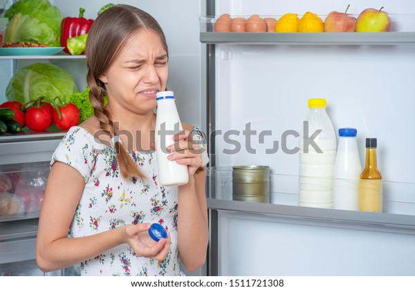 Beautiful young teen girl holding bottle of milk, sniffing with bad odor while standing near open fridge in kitchen at home. Portrait of pretty child choosing food. Milk went bad in refrigerator.