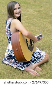 A beautiful young teen girl outdoors with a guitar.