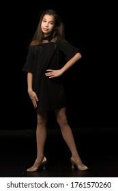 Beautiful young teen girl studio photo on black background