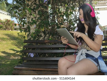Beautiful young teenage girl wearing a set of headphones and using a tablet in a park. Concept Image.