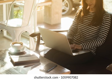Beautiful young teenage woman freelance work with laptop at coffee shop in with sun light, freelance lifestyle conceptual