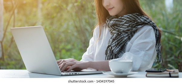 Beautiful young teenage woman freelance work with laptop with a cup of latte on sun light, freelance lifestyle conceptual