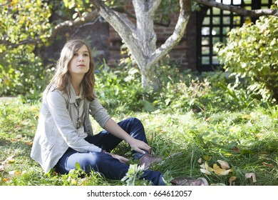 Beautiful young teenager sitting on a trunk of a tree