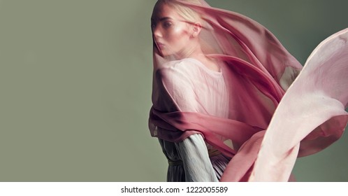A beautiful young tender girl in a chiffon dress is covered with a drapery made of thin fabric that develops in the wind.fashion, beauty, makeup, cosmetics, beauty salon, style, personal care, posture