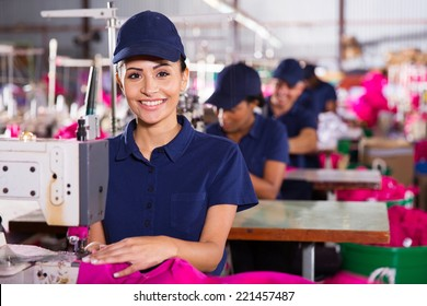 beautiful young textile machinist using sewing machine in clothing factory