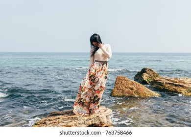 a beautiful young thin girl in full growth with dark long straight hair with a skirt with flowers stands on a rock in the sea