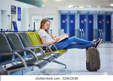Beautiful young tourist girl with backpack and carry on luggage in international airport, reading a book while waiting for her flight