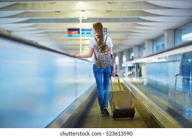 Beautiful young tourist girl with backpack and carry on luggage in international airport, on travelator