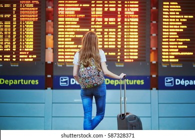 Beautiful young tourist girl with backpack and carry on luggage in international airport, near flight information board
