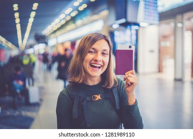 "Beautiful young tourist girl in international airport, taking selfie with passport and boarding pass ready for boarding and fly. Doing gesture ""ok"" with other hand"