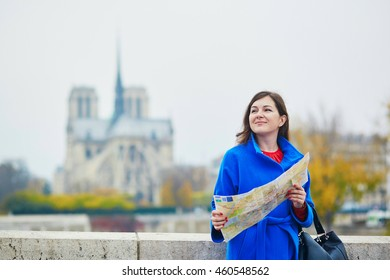 Beautiful young tourist in Paris, using map near Notre-Dame cathedral