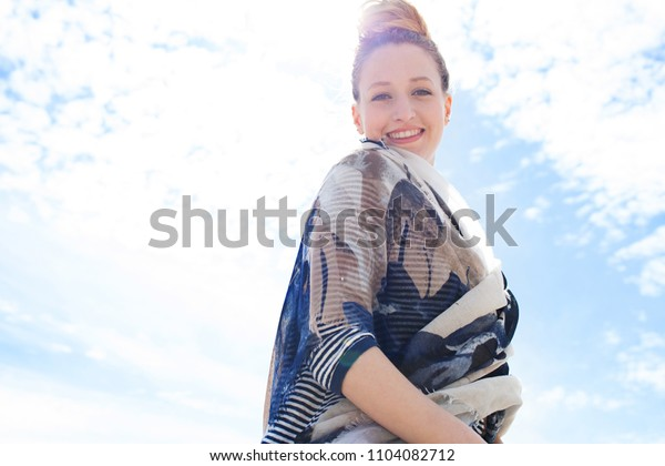 Beautiful young tourist woman holiday coastal beach destination against sunny blue sky, looking smiling with flare in nature, outdoors. Healthy female in sunshine light, leisure recreation lifestyle.