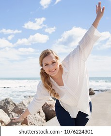 Beautiful young tourist woman visiting coastal beach destination on holiday, playful stretching arms looking smiling, fun outdoors. Female energy blue sunny sky, leisure recreation lifestyle, wellness