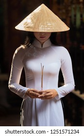 Beautiful, young and traditionally dressed Vietnamese woman in an ancient temple.