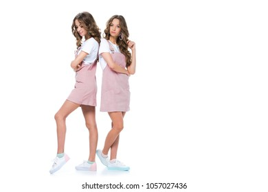 beautiful young twins standing back to back isolated on white