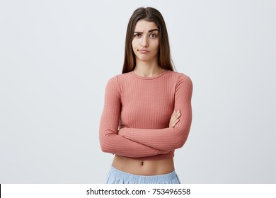 Beautiful young unhappy Caucasian brunette girl with long hair in fashionable outfit crossing hands, looking in camera with sarcastic expression, can't believe her boyfriend was with friend last night