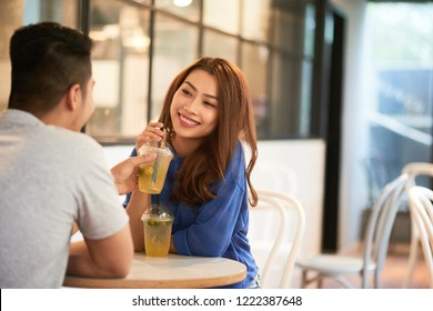 Beautiful young Vietnamese woman tasting iced tea of her boyfriend in cafe