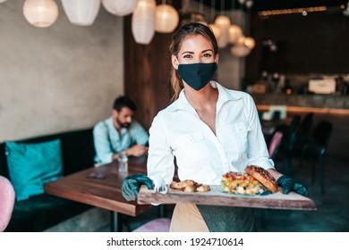 Schöne junge Kellnerin mit Gesichtsschutzmaske, die köstliche Burger bis mittelalterliche männliche Kunden serviert. Corona Virus und kleine Unternehmen ist offen für Arbeitskonzept.