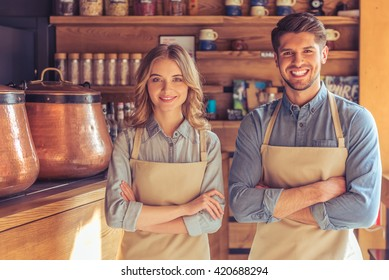 Beautiful young waitress and handsome young waiter in aprons are looking at camera and smiling while standing with crossed arms in the cafe