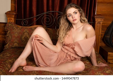 Beautiful young wavy haired blonde in a peach tunic