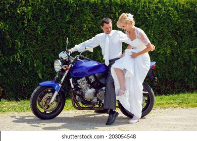 beautiful young wedding couple, blonde bride with flower try sit to motorcycle with her groom