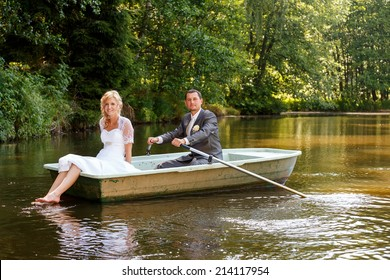 beautiful young wedding couple, blonde bride with flower and her groom just married on small boat at pond with evening sun