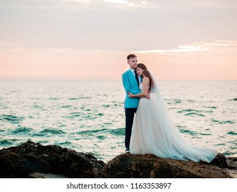 Beautiful young wedding couple standing on sea shore with rocks. Newlyweds spend time together: embrace, kiss and care for each other. Love concept. Bride smiling to groom.
