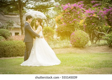 Beautiful Young wedding couple with white umbrellas standing on a green lawn. Man hugging young woman. Vintage tone.