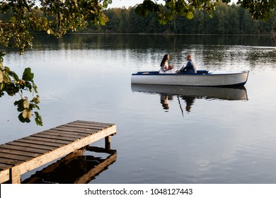 beautiful young wedding couple,bride with flower and her groom just married on small boat at pond with evening sun.happy loving couple rowing a small boat on a lake.