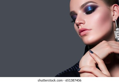 Beautiful young white girl close-up in a black jacket on a gray background in the studio. Makeup - blue smokeys, shades of metallic, lipstick bright glossy shine. Hairstyle - smoothly combed hair.