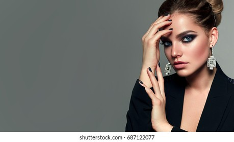 Beautiful young white girl close-up in a black jacket on a gray background in the studio. Fashion, beauty, make-up, cosmetics, hairdo, beauty salon, styling, costume jewelery.