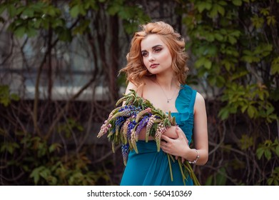 The beautiful young white girl keeps flowers in a blue dress. Street portrait. The charming young woman with a make up and a hairstyle
