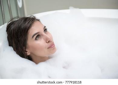 Beautiful young white woman enjoy relaxing in bubble bath. Resting, eye open, smiling. White caucasian woman.