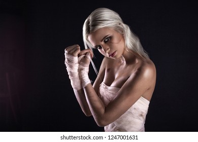 Beautiful young white-haired warrior girl with bandage on hands in light underwear on dark background