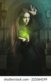 Beautiful young witch casting a spell  . Halloween and fantasy studio shot