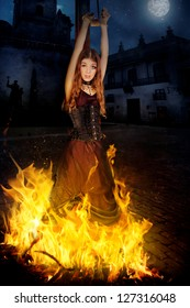 Beautiful young witch in the flames of fire