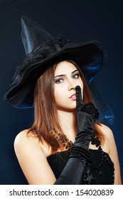 """beautiful young woma in witch or fairy costume and fancy hat for halloween party, showing """"hush!"""" sign holding finger on her lips over dark background"""