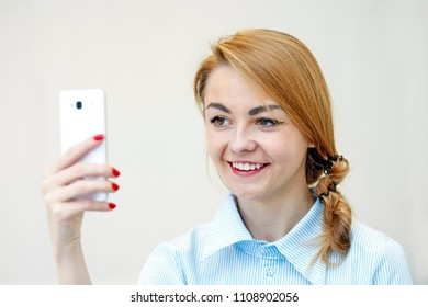 beautiful young womam smiles and takes a photo on mobile on white background, portrait
