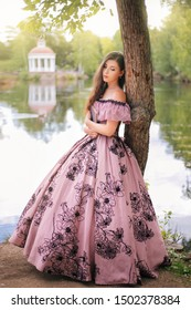 A beautiful young woman in a 19th-century dress stands with a book in a park. Romantic girl at the pond.