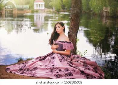 A beautiful young woman in a 19th-century dress sits with a book by the pond. Romantic girl in the park.