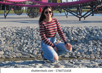 beautiful young woman about 20 years old, caucasian, long straight black hair, sculptural body, crouched in an area full of stones, wearing ripped jeans, striped blouse and sunglasses, blue sky