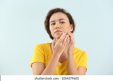 Beautiful young woman with acne problem on light background