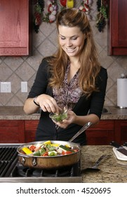 Beautiful young woman adding chopped basil to dish on stove in kitchen.